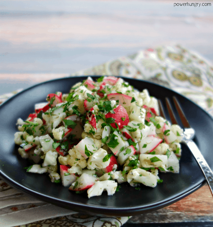 chopped radish & cauliflower salad on a black plate